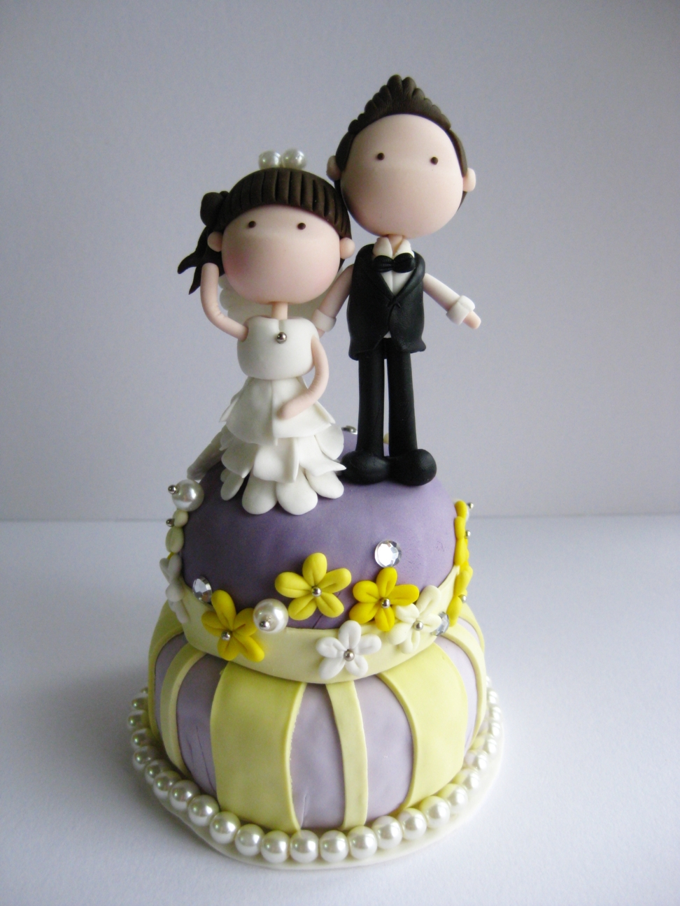 wedding clay cake topper standing on top of a cake not edible